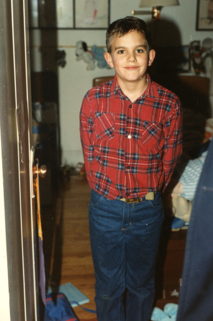 Me as an eight year-old wearing an awkward plaid flannel shirt tucked into blue jeans. This time period is one of the last times I remember not worrying a whole lot about how I was seen as a boy and mental health things hadn't started yet.