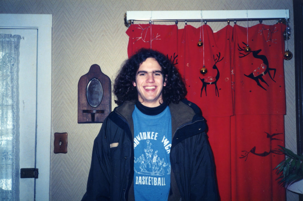 Me with long hair at 17 years-old. My big smile has been a good cover for mental health struggles.