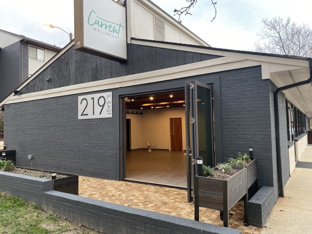 Front exterior of Current Wellness with patio, planters, and open folding doors leading into Movement Studio space (where fitness and yoga classes are held)